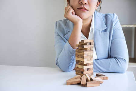 Alternative Risk and Strategy in Business, Image of Stressed, worry, Business woman gambling placing making wooden block hierarchy on the tower to planning and development to successful.
