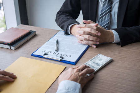 Dishonest cheating in illegal money, Businessman giving bribe money the form of dollar bills to while give success the deal to contract agreement, Bribery and corruption concept. Stock Photo