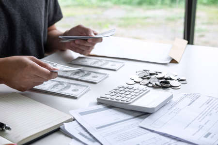 Images of stacking coin pile and Husband using calculator to calculating expenditure receipt bills of various activity cost and expenses in home office and written make report to plan of spent.
