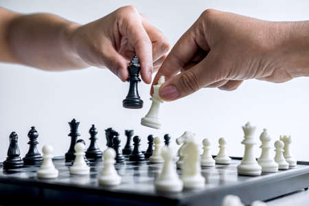 Businessman and businesswoman playing chess and thinking about strategy crash overthrow the opposite team and development analysis for win and successful. Stock Photo - 131727127