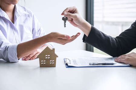 Estate agent giving house keys to client after signing agreement contract real estate with approved mortgage application form, concerning mortgage loan offer for and house insurance. Stock Photo - 132719516