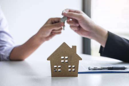 Estate agent giving house keys to client after signing agreement contract real estate with approved mortgage application form, concerning mortgage loan offer for and house insurance. Stock Photo
