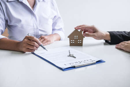Estate agent broker reach contract form to client signing agreement contract real estate with approved mortgage application form, buying or concerning mortgage loan offer for and house insurance. Stock Photo