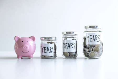 Images of coin in piggy bank for step up growing business to profit of each years and saving with piggy bank, Saving money for future plan education and retirement fund concept. Stock Photo - 132719518