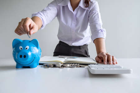 Woman putting coin in blue piggy bank for step up growing business to profit and saving with piggy bank, Saving money for future plan and retirement fund concept.