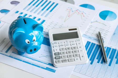 Business finance with report document, calculator, stacking coins and piggy bank for step up growing business to profit and saving with wealth management.