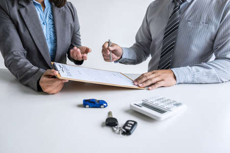 Realtor agent manager holding rental contract form to businessman client for decide signing to agreement, renting considering vehicle car insurance. Stock Photo