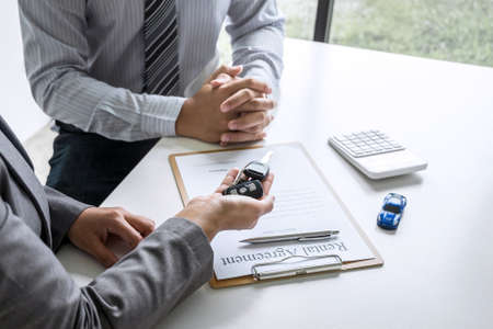 Car rent agent manager holding key of new car giving to businessman client after signing good deal agreement contract, renting considering vehicle.