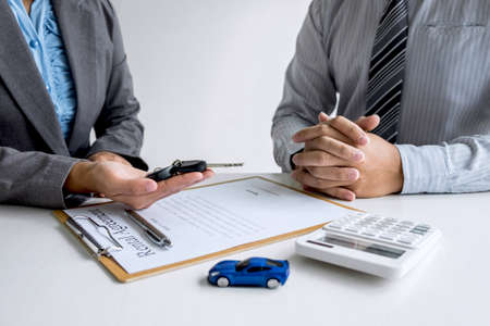 Car rent agent manager holding key of new car giving to businessman client after signing good deal agreement contract, renting considering vehicle. Stock Photo - 131734007