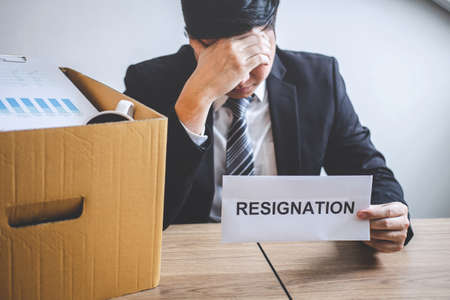 Stressed businessman will prepared being sending resignation letter to company and packing belongings and files into brown cardboard box, changing and resigning from work concept. Фото со стока - 138172461