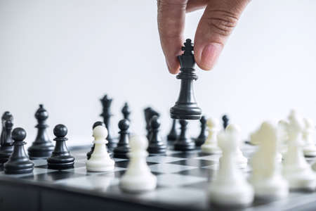 Business woman playing chess and thinking strategy about crash overthrow the opposite team and development analysis for win and successful. Imagens