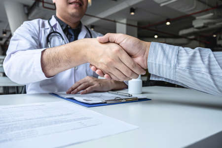 Doctor having shaking hands to congrats with patient after recommend sickness treatment while discussing explaining his symptoms and counsel diagnosis health, healthcare and assistance concept.