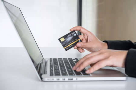 Business woman consumer holding credit card and typing on laptop for online shopping and payment make a purchase on the Internet, Online payment, networking and buy product technology. Фото со стока - 138172469