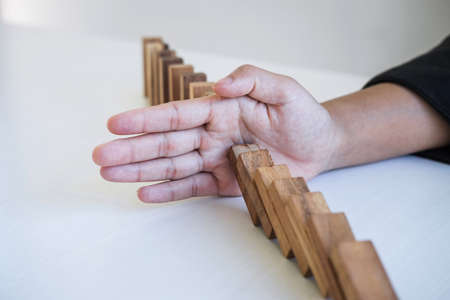 Risk and Strategy in Business, Image of hand stopping falling collapse wooden block dominoes effect from continuous toppled block, prevention and development to stability. Фото со стока - 138172470