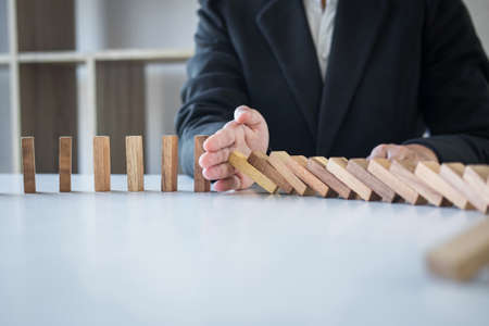 Risk and Strategy in Business, Image of hand stopping falling collapse wooden block dominoes effect from continuous toppled block, prevention and development to stability. Фото со стока - 138175348
