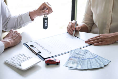 Car rent agent manager sending key of new car giving to woman client after signing good deal agreement contract, renting considering vehicle. Фото со стока - 138175349