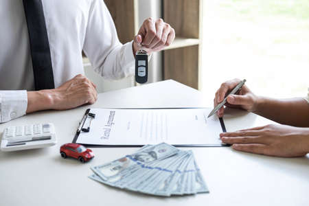 Car rent agent manager sending key of new car giving to woman client after signing good deal agreement contract, renting considering vehicle. Stock Photo