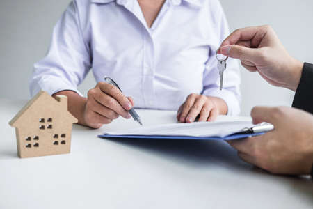Estate agent giving house keys to client after signing agreement contract real estate with approved mortgage application form, concerning mortgage loan offer for and house insurance. Фото со стока - 138085149