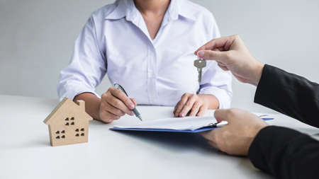 Estate agent giving house keys to client after signing agreement contract real estate with approved mortgage application form, concerning mortgage loan offer for and house insurance. Фото со стока - 138085150