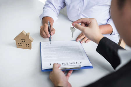 Estate agent giving house keys to client after signing agreement contract real estate with approved mortgage application form, concerning mortgage loan offer for and house insurance. Фото со стока - 138085151