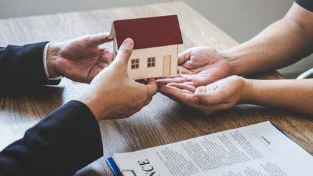Estate agent giving house and keys to client after signing agreement contract real estate with approved mortgage application form, concerning mortgage loan offer for and house insurance.