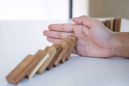 Risk and Strategy in Business, Image of hand stopping falling collapse wooden block dominoes effect from continuous toppled block, prevention and development to stability. Фото со стока - 138175356