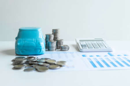 Images of stacking coins pile and blue smiling piggy bank to growing and savings with money box, Saving money for future plan and retirement fund concept.