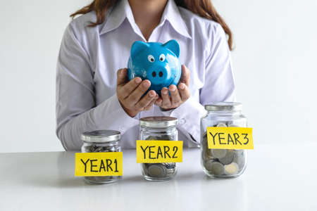 Woman putting coin in blue piggy bank for step up growing business to profit of each years and saving with piggy bank, Saving money for future plan and retirement fund concept. 写真素材