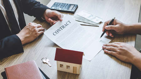 Estate agent broker reach contract form to client signing agreement contract real estate with approved mortgage application form, buying or concerning mortgage loan offer for and house insurance. Фото со стока - 138175369