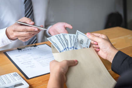 Dishonest cheating in illegal money, Business woman giving bribe money the form of dollar bills to while give success the deal to contract agreement, Bribery and corruption concept.