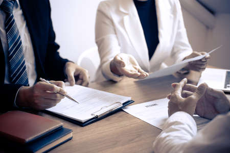 Employer or committee holding reading a resume with talking during about his profile of candidate, employer in suit is conducting a job interview, manager resource employment and recruitment concept. Stock Photo