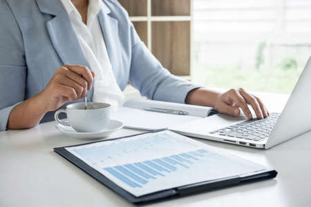Business woman accountant financier working audit and calculating expense financial annual report balance sheet statement, doing finance checking document and making notes on report paper. Фото со стока - 137697822