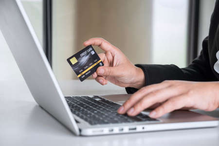 Business woman consumer holding credit card and typing on laptop for online shopping and payment make a purchase on the Internet, Online payment, networking and buy product technology. Фото со стока - 137697802