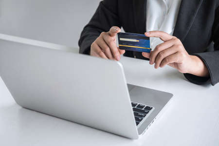Business woman consumer holding credit card and typing on laptop for online shopping and payment make a purchase on the Internet, Online payment, networking and buy product technology. Фото со стока - 137697839