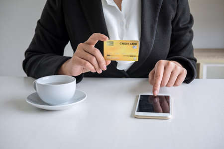 Young woman consumer holding smartphone, credit card and typing for online shopping and payment make a purchase on the Internet, Online payment, networking and buy product technology. Фото со стока - 137697691