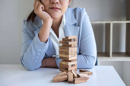 Alternative Risk and Strategy in Business, Image of Stressed, worry, Business woman gambling placing making wooden block hierarchy on the tower to planning and development to successful. Фото со стока - 138175384