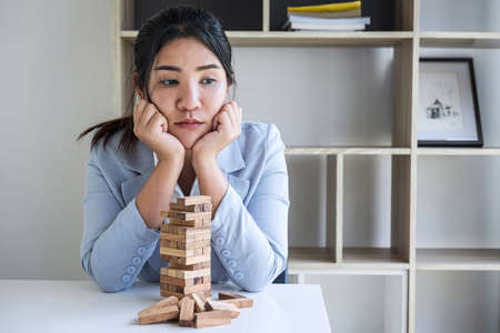 Alternative Risk and Strategy in Business, Image of Stressed, worry, Business woman gambling placing making wooden block hierarchy on the tower to planning and development to successful. Фото со стока - 138172525