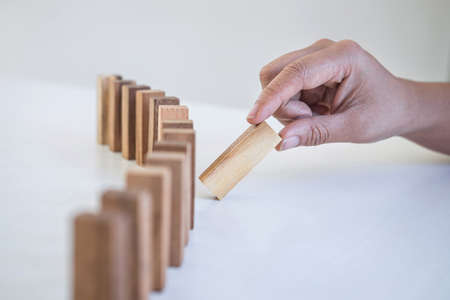 Risk and Strategy in Business, Image of hand gambling placing wooden block on a line of domino, prevention and development to stability. Фото со стока - 138172529