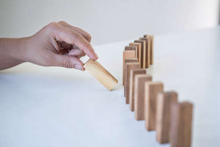 Risk and Strategy in Business, Image of hand gambling placing wooden block on a line of domino, prevention and development to stability. Фото со стока - 138172533