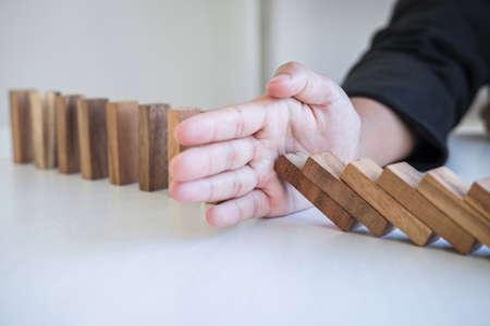 Rischio e strategia negli affari, immagine della mano che ferma la caduta dell'effetto domino del blocco di legno del crollo dal blocco rovesciato continuo, prevenzione e sviluppo alla stabilità. Archivio Fotografico