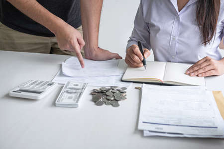 Images of Husband and wife using calculator to calculating expenditure receipt bills of various activity cost and expenses in home office and written make report to plan of spent in future. Stock fotó