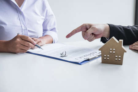 Estate agent broker reach contract form to client signing agreement contract real estate with approved mortgage application form, buying or concerning mortgage loan offer for and house insurance.