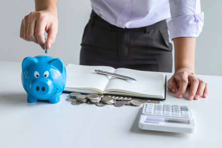 Woman putting coin in blue piggy bank