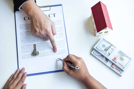 Estate agent broker pointing contract form to client signing agreement contract real estate with approved mortgage application form, buying or concerning mortgage loan offer for and house insurance. Archivio Fotografico