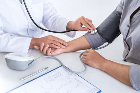 Doctor using a measuring blood pressure checking patient with examining, presenting results symptom and recommend treatment method, Healthcare and medical concept.