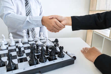 Businessman and businesswoman shaking hands after playing chess and thinking about strategy crash overthrow the opposite team and development analysis for win and successful.