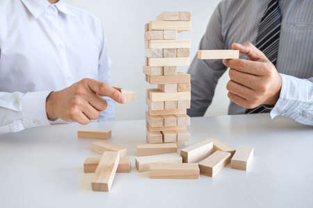 Alternative Risk and Strategy in Business, Hand of business team cooperative gambling placing making wooden block hierarchy on the tower to collaborative planning and development to successful.