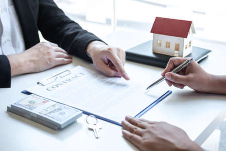Estate agent broker pointing contract form to client signing agreement contract real estate with approved mortgage application form, buying or concerning mortgage loan offer for and house insurance.