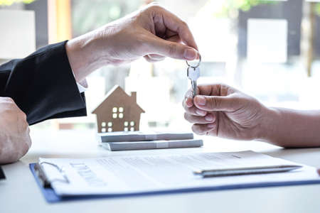 Estate agent giving house keys to client after signing agreement contract real estate with approved mortgage application form, concerning mortgage loan offer for and house insurance. Archivio Fotografico