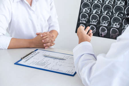 Professor Doctor having conversation with patient and holding x-ray film while discussing explaining symptoms or counsel diagnosis health, healthcare and assistance concept. Archivio Fotografico